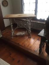 Pie de máquina coser antigua con un sobre en madera natural preparado para mesa
