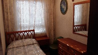 Dormitorio de madera con una cama y coqueta